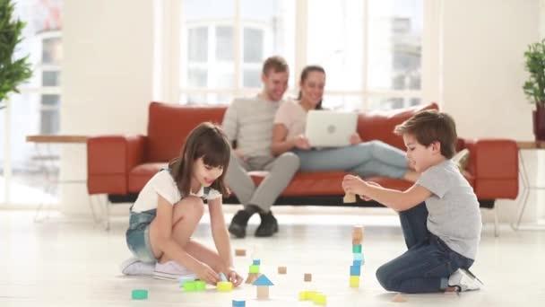 Děti si hrají na podlaze, zatímco šťastní rodiče odpočívají na gauči