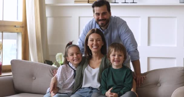 Glückliche Eltern, die mit ihren Kindern auf der Couch sitzen und in die Kamera schauen