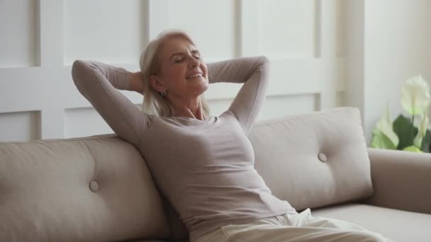 Happy middle aged woman relaxing sit on couch at home
