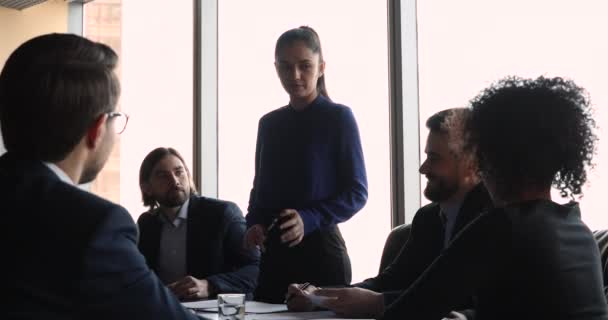 Female leader speak to diverse employees at formal group meeting