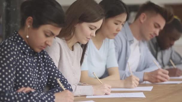 Soustředění studenti smíšeného plemene sedící u stolu na výchovné přednášce.