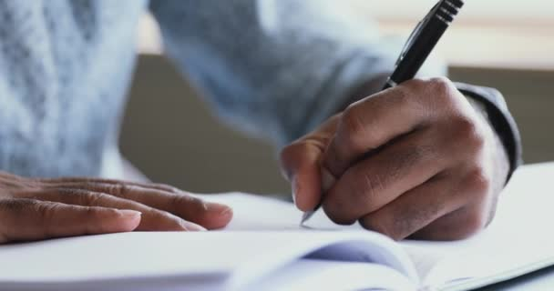 African left-handed businessman holding pen writing in organizer, close up