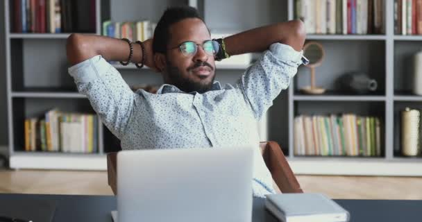 Relaxed young african businessman rest sit at work desk