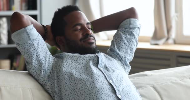 Serene african man resting on couch eyes closed enjoy nap