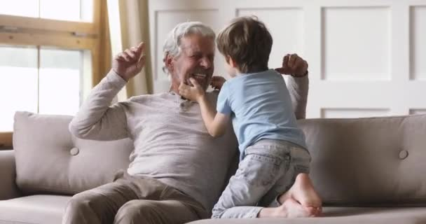 Cheerful old grandpa and cute grandson laughing playing at home