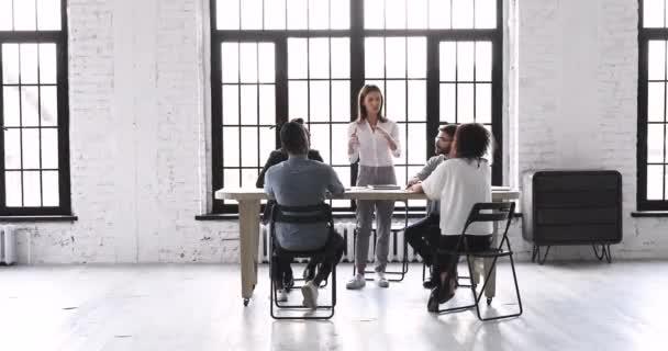 Vedoucí pracovnice na týmové poradě v moderních kancelářských prostorách