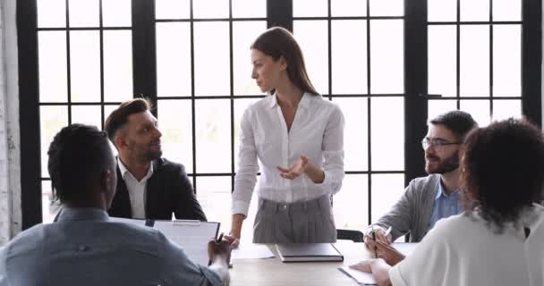 Confident businesswoman manager speaking at team meeting stand at table