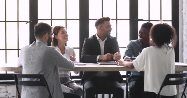 Happy friendly multiracial business team talking sit at office table