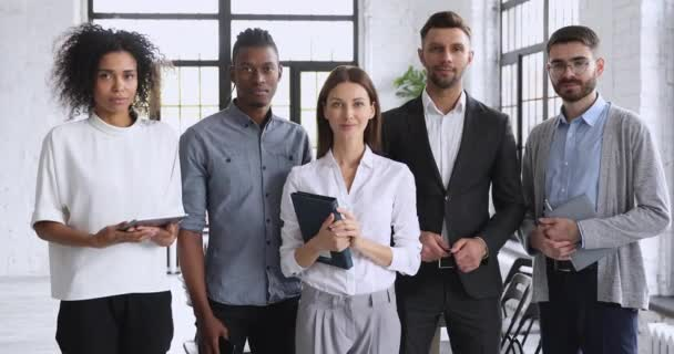 Happy multiracial team stand together look at camera in office