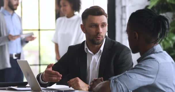 Male salesman employer handshake african client sign lease agreement