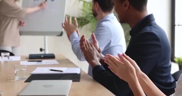 Různí obchodníci diváci sedí u konferenčního stolu tleskat ruce