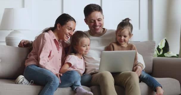 Veselí rodiče a děti dcery smějící se pomocí notebooku doma