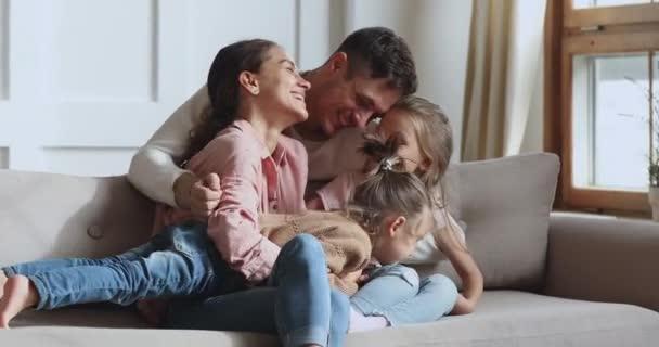 Šťastná milující rodina nebo čtyři rozesmáté objímání mazlení na pohovce