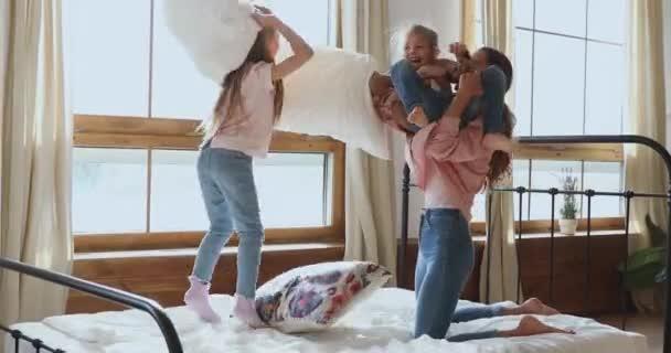Anya és két aranyos lány párnacsata az ágyban.