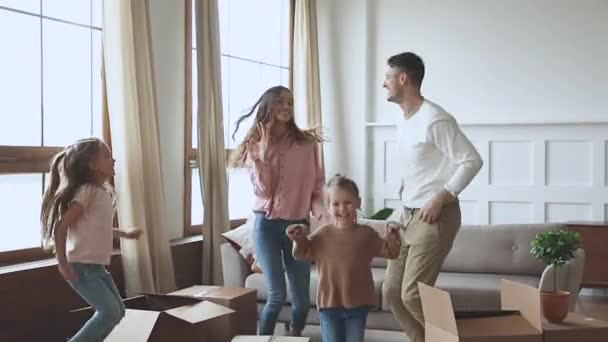 Happy parents and children dancing celebrating moving day, slow motion