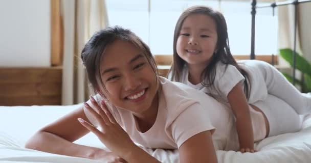 Happy asian mom and daughter looking at camera in bed