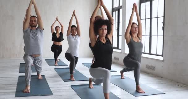 Diverse Sportler, die an Yoga-Übungen mit Virabhadrasana teilnehmen