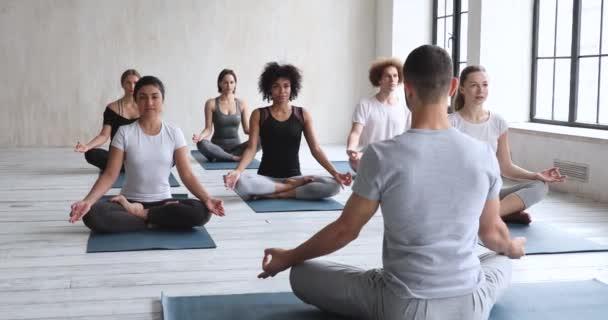Mužský trenér a multietničtí lidé sedící v lotosové poloze meditující