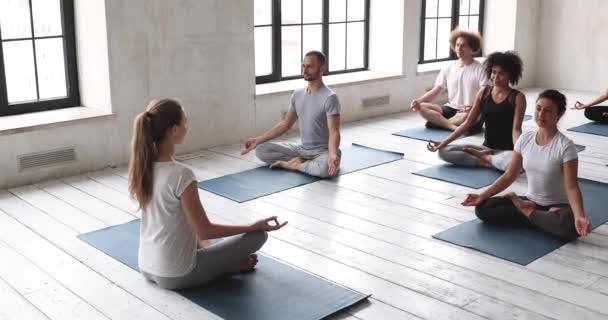Multietničtí lidé praktikující jógu sedící v lotosové poloze dělají meditaci