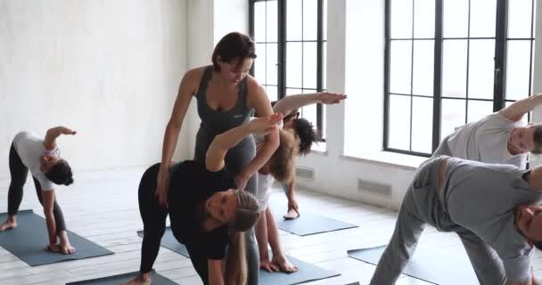 Instruktor jógy pomáhá dívce správně vykonávat rozšířenou polohu v bočním úhlu