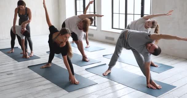 Female yoga instructor help to people perform correctly Utthita Parsvakonasana