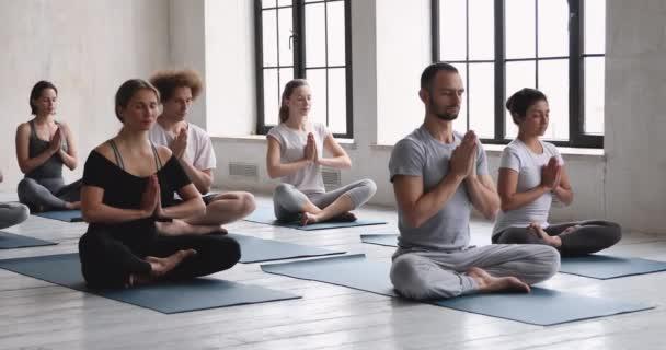 A lótuszban ülő sokszínű emberek meditációja közben a jógát gyakorolják a házban.