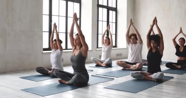 Multiethnic people and female yoga coach performing asana meditating indoors