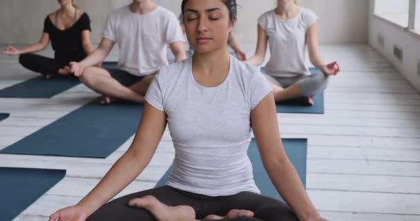 Indiai etnikai nő és más, jóga órán meditáló munkatársak