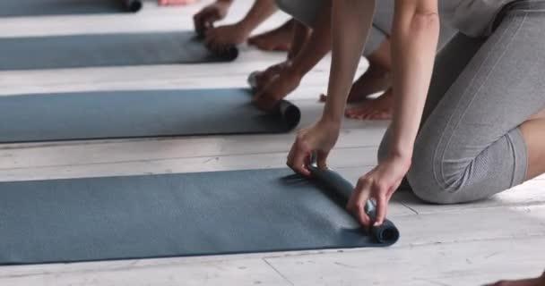 Detailní ruce multi-etnické ženy složit jóga rohože po cvičení