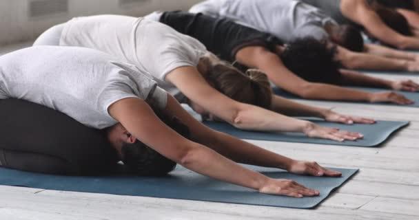 Během jógy sedm multietnických lidí cvičí dětský postoj