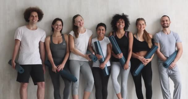 Multi-ethnic millennial people standing holding yoga mats posing for camera