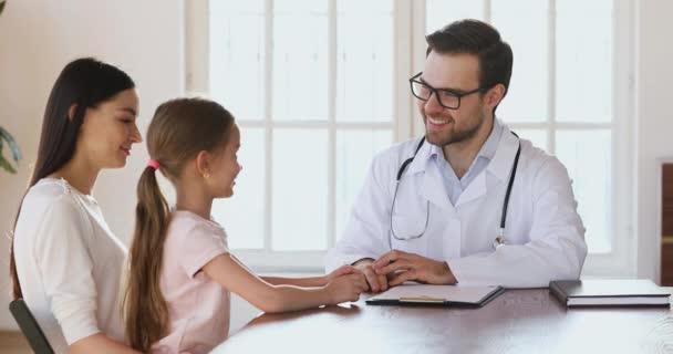 fürsorgliche männliche Arzt sprechen streicheln Kopf von niedlichen Kind Mädchen