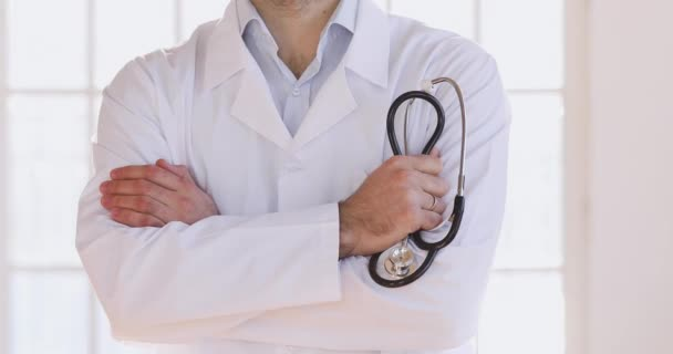 Arzt trägt Arztkittel und hält Stethoskop in die Kamera