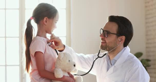 Lächelnder Kinderarzt mit Stethoskop untersucht süßes kleines Mädchen