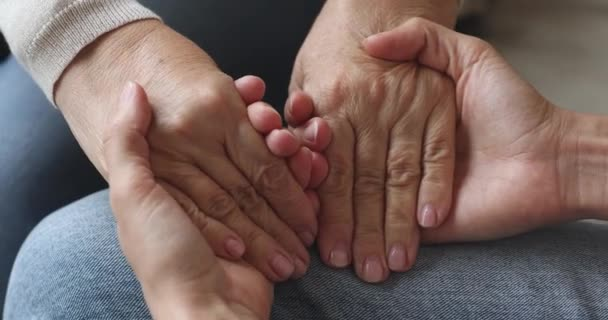 Young woman hold old female hands giving support concept, closeup