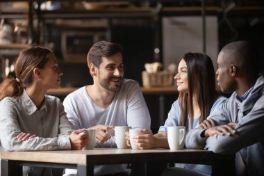 Diverse young people meeting in cafe drinking coffee