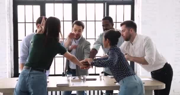 Boldog többnemzetiségű üzleti csoport verem össze a kezét a találkozó asztal