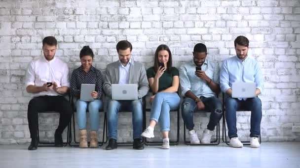 Multiracial businesspeople sit on chairs waiting for interview using devices