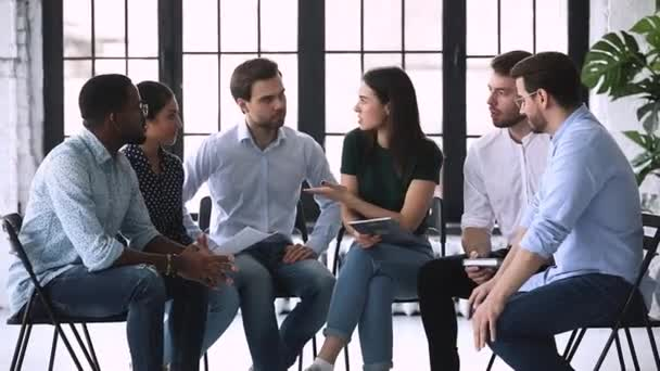 Female coach communicate with multiethnic business team sitting in circle