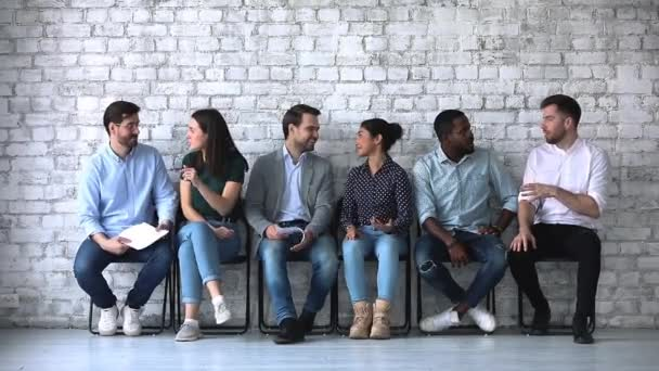 freundliche multiethnische Geschäftsleute im Gespräch sitzen auf Stühlen in Reihe