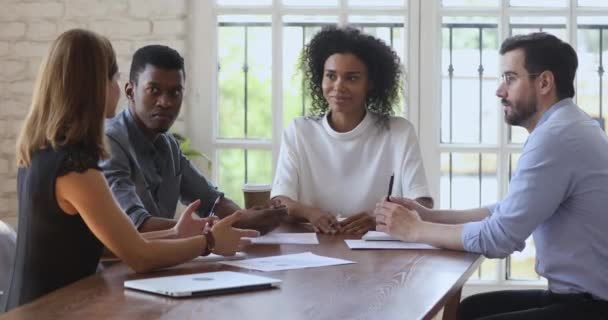 Focused mixed race coworkers discussing project details at workplace.