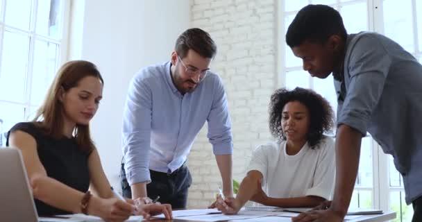 Skupina mladých multiraciálních pracovníků, kteří analyzují výsledky výzkumu v papírové zprávě.