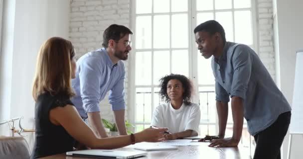 Multiraciální mužští spolupracovníci dává plácnutí na setkání.