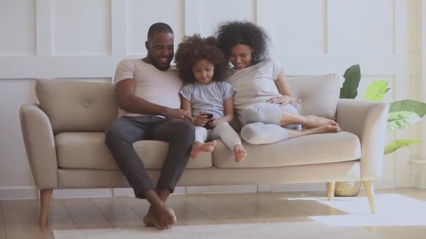 Kleines Mädchen zeigt Eltern lustige Videos auf dem Smartphone.
