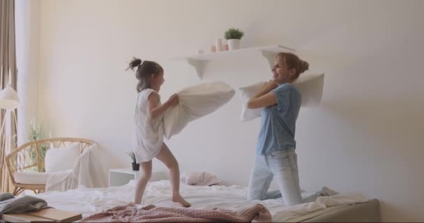 Overjoyed family fighting with pillows on bed.