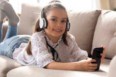 Portrait of smart little girl in headphone using cell
