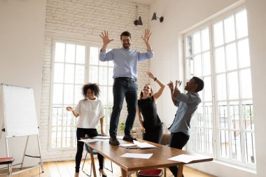 Excited leader dancing with diverse business team in boardroom
