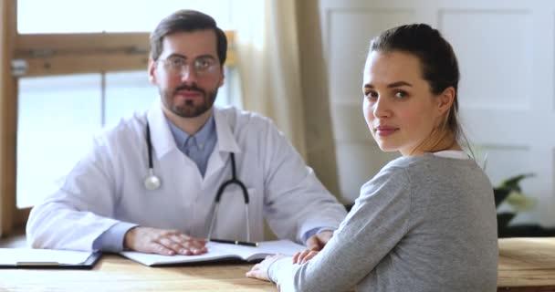 Usmívající se pacientka dívající se na kameru u mužského lékaře, portrét