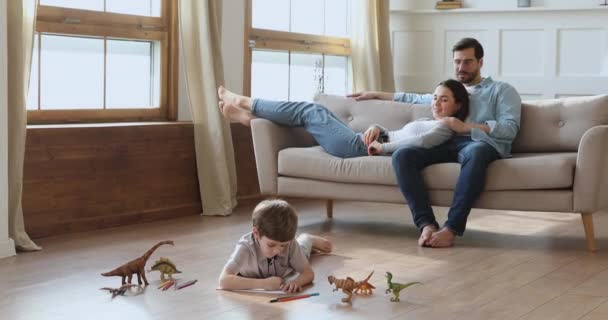 Kid son drawing on floor while parents relaxing on sofa