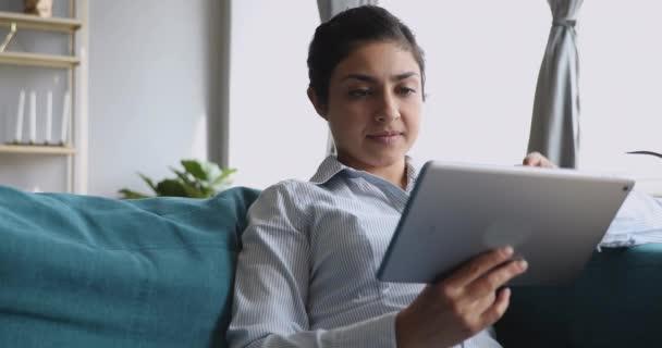 glückliche indische Mädchen mit digitalen Tablet-Anwendungen sitzen auf dem Sofa